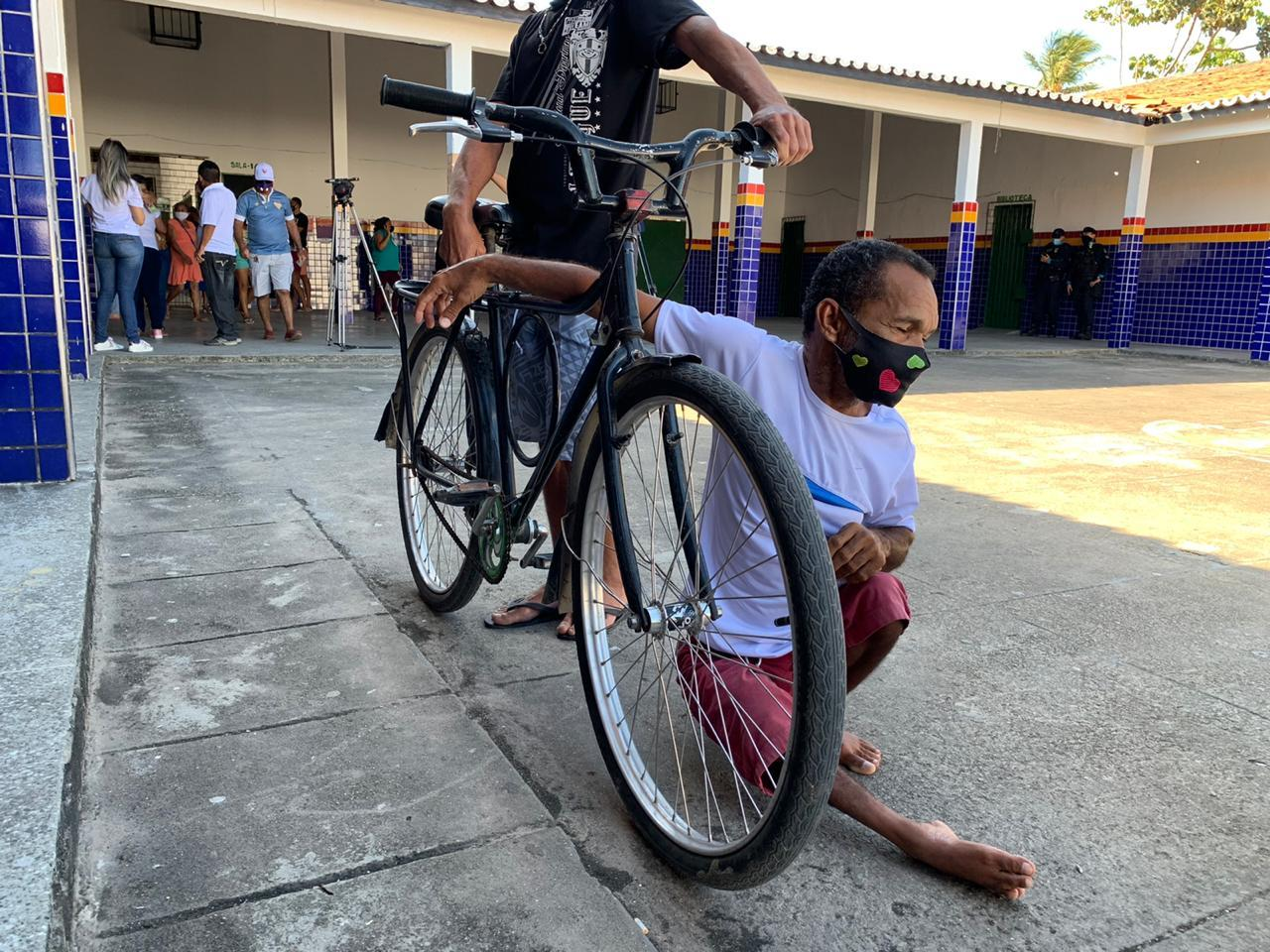 Eleitor com dificuldade de mobilidade sentado no chão ao lado da bicicleta do irmão