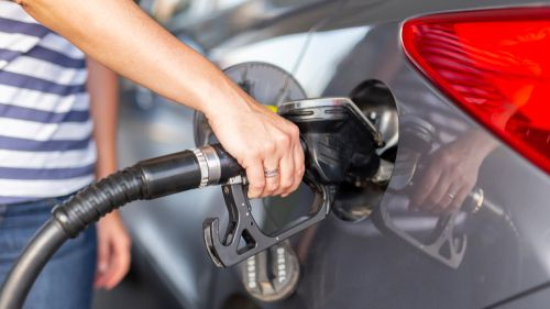 Mulher reabastecendo o carro no posto de gasolina; reabastecimento do tanque do carro em um posto de gasolina