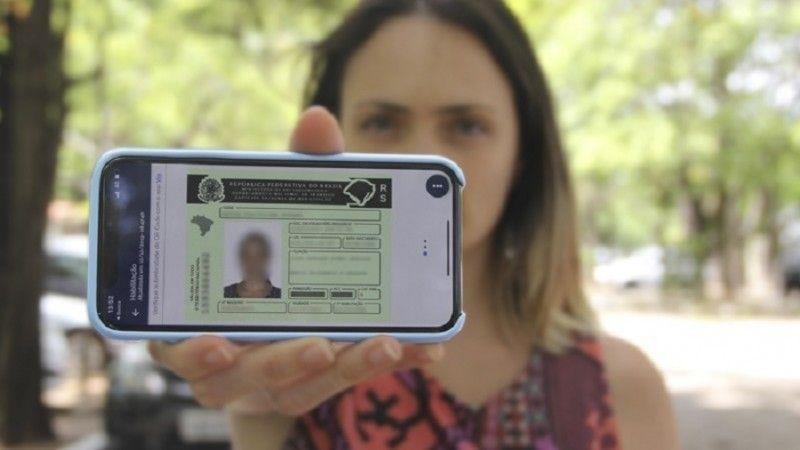 Mulher branca e de cabelos loiros segurando iPhone mostrando a CNH digital