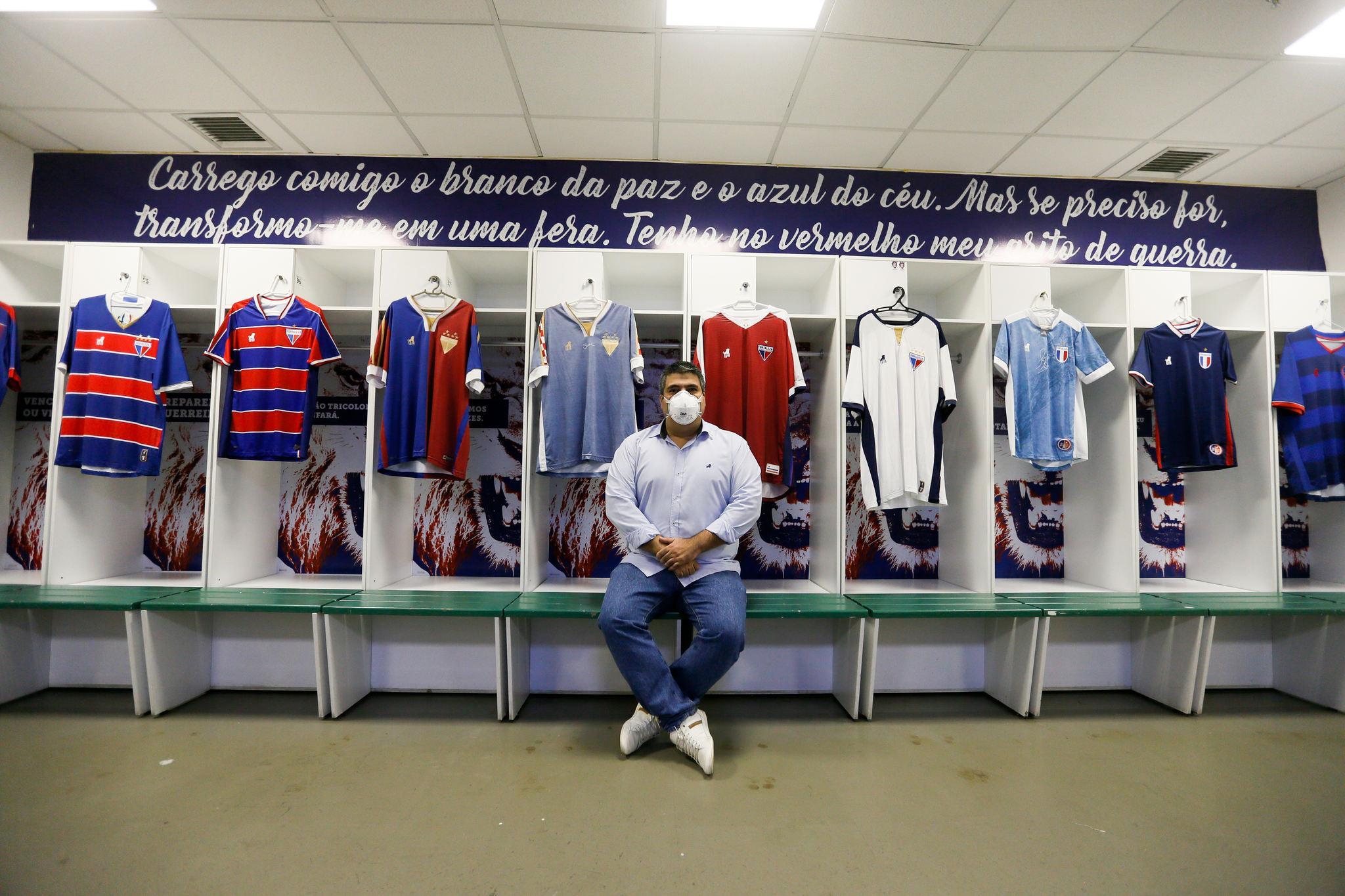 Bruno Bayma exibe as camisas da marca própria do Fortaleza no vestiário do clube, na Arena Castelão