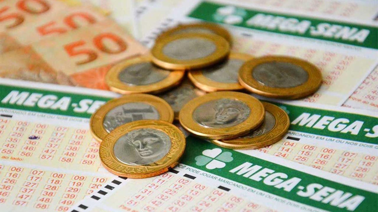 Cartelas da Mega Sena em torno de cédulas e moedas