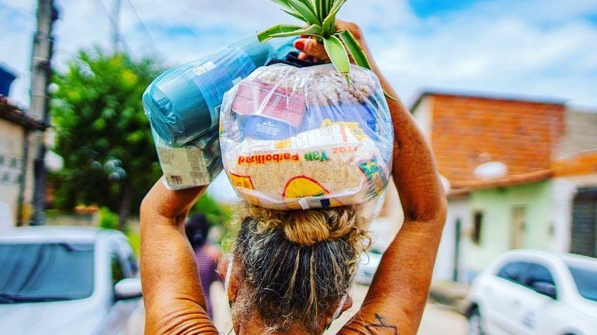 Mulher carrega cesta básica no Ceará
