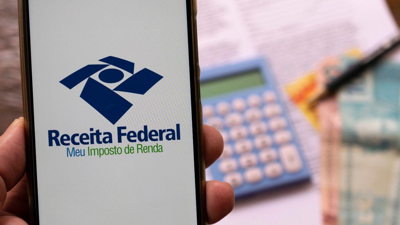 Celular em mãos com pedido de declaração de imposto de renda da Receita Federal. Foco seletivo. irpf 2021.