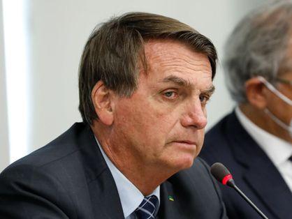 Presidente Jair Bolsonaro ao lado de ministro da Economia, Paulo Guedes, ao fundo