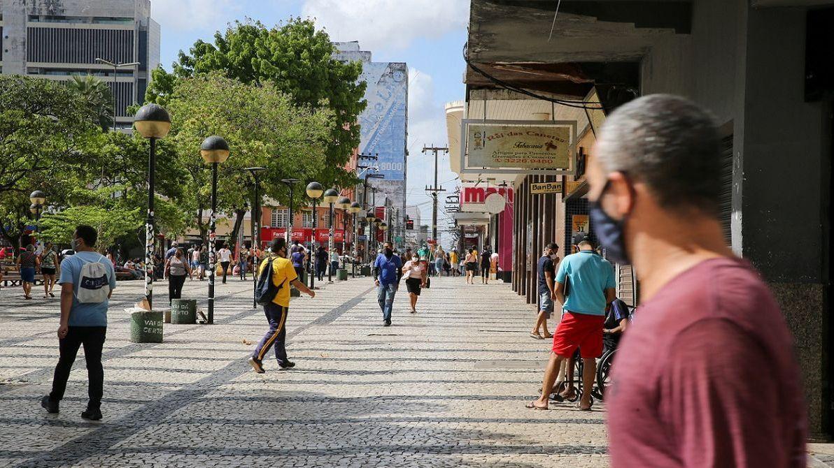 Foto da Praça do Ferreira, no Centro de Fortaleza. Pessoas passeiam usando máscara. O comércio do entorno reabrirá a partir da semana que vem