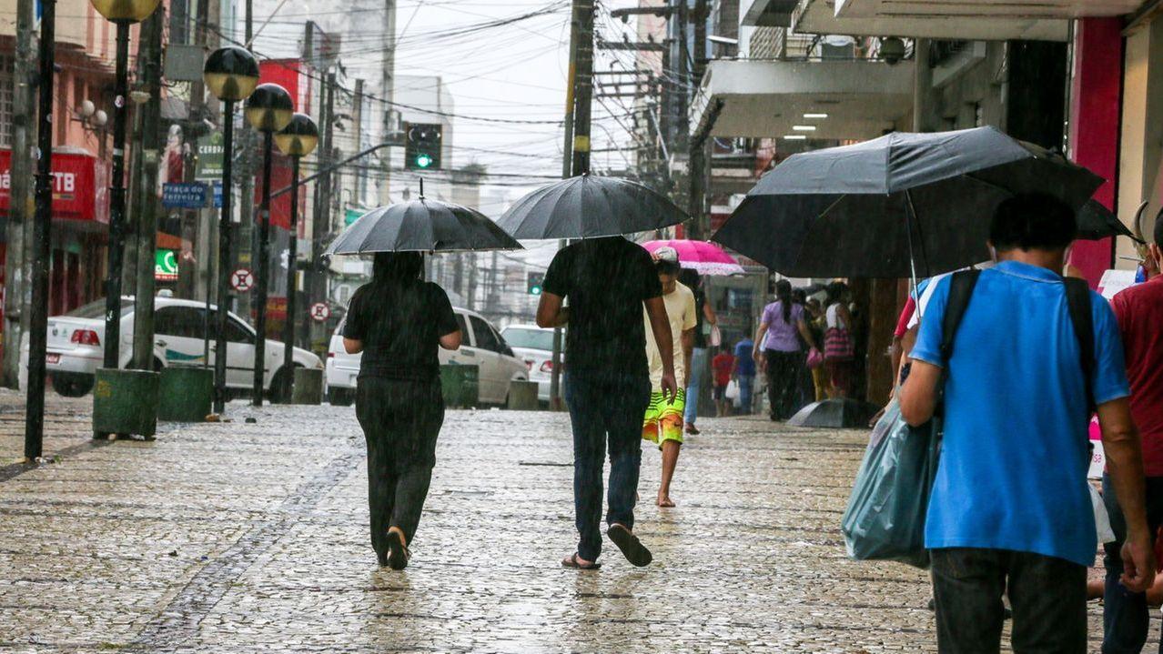 Pessoas passeiam usando guarda-chuva