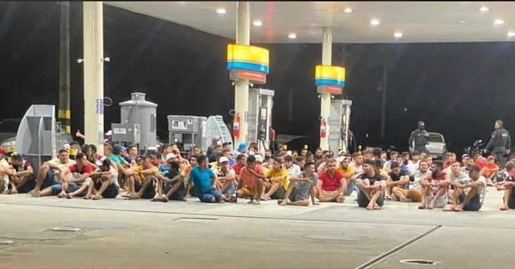 Pessoas sentadas no chão em posto de combustível