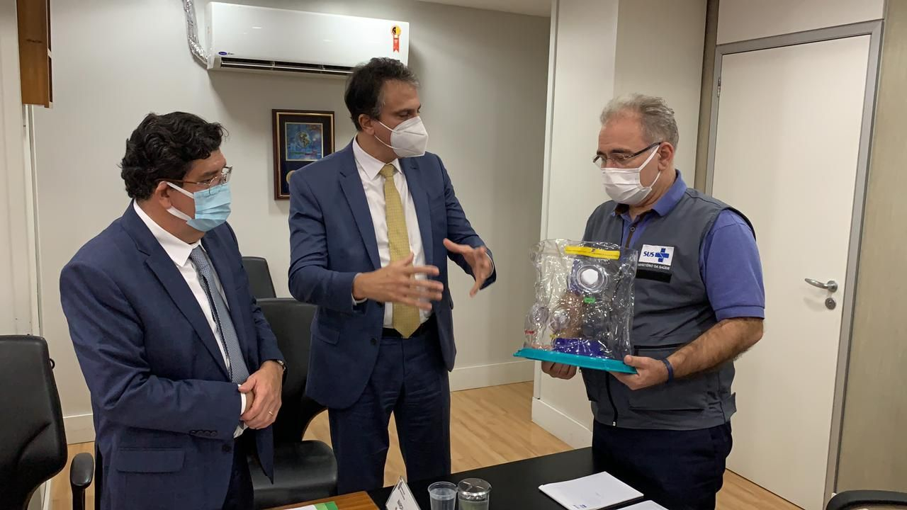 O ministro da Saúde, Marcelo Queiroga, segura uma unidade do Capacete Elmo enquanto o governador Camilo Santana e o secretário de Saúde, Dr. Cabeto, apresentam o equipamento