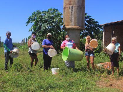 Em frente a uma caixa d'água/chafariz, famílias mostram baldes vazios, denunciando escassez. Projeto de abastecimento hídrico não foi concluído.