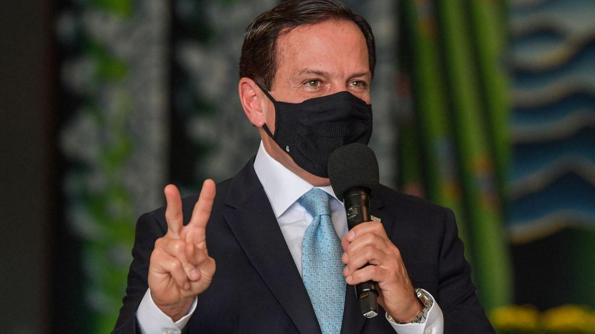 Governador de São Paulo João Doria fazendo símbolo de 2 com o dedo e segurando um microfone durante evento