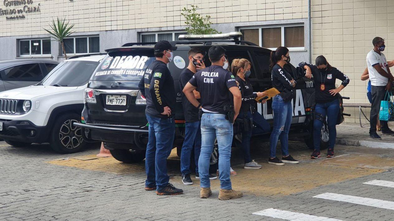 Agentes da Polícia Civil parados ao lado de viatura