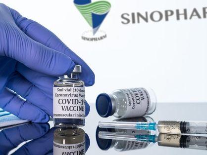 Frasco de vacina sendo manuseado por profissional da saúde
