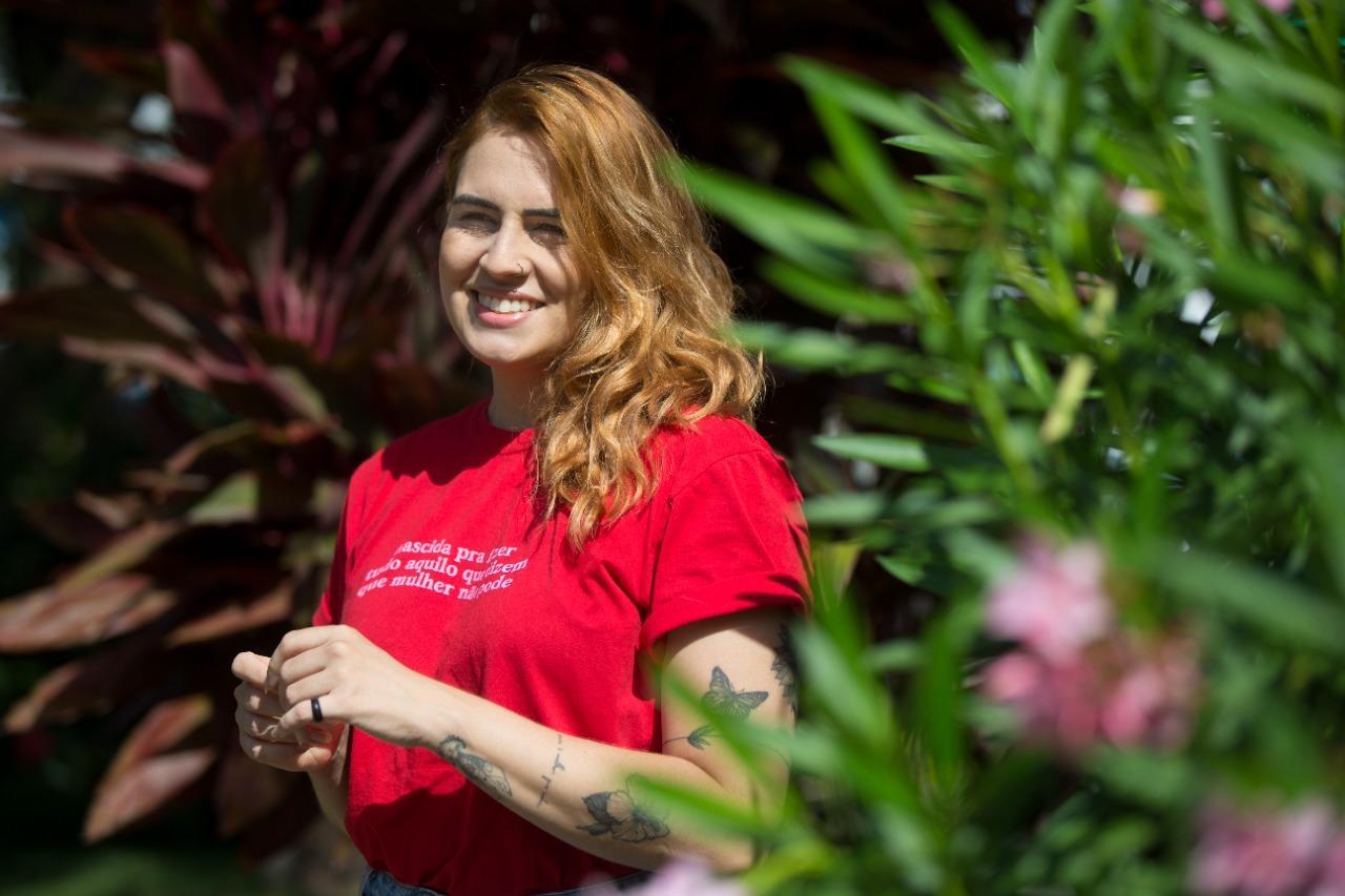 Neyla, que tem bordeline, sorri em jardim.