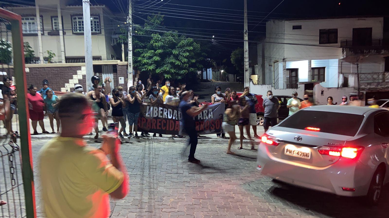 Populares aguardando a saída de Maria Aparecida da prisão, segurando cartazes de apoio