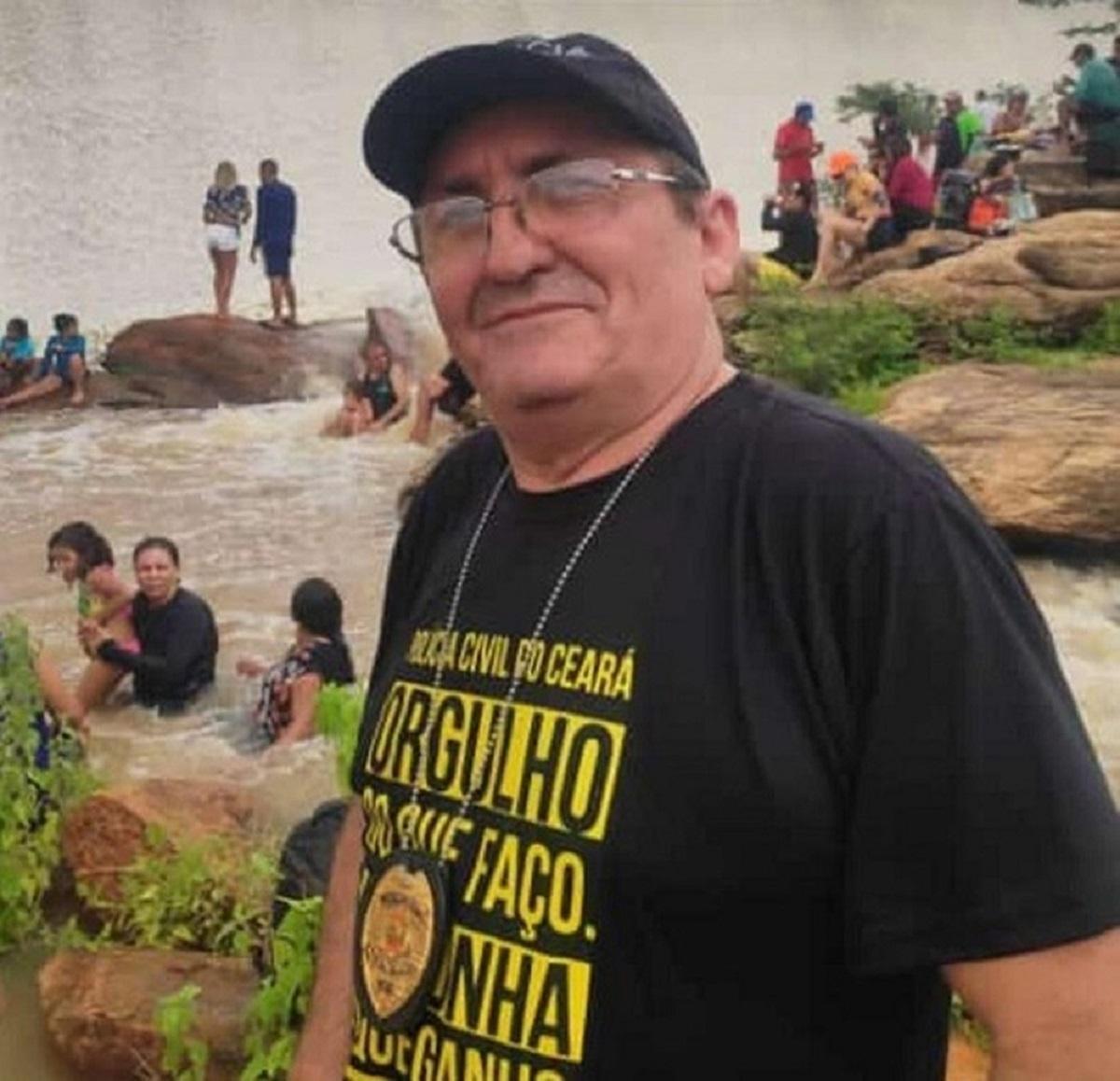 Foto do escrivão morto dentro da Delegacia Regional de Tauá. Na imagem, Aloizio Alves está sorrindo levemente, com brasão policial no pescoço em um ambiente rodeado por areia