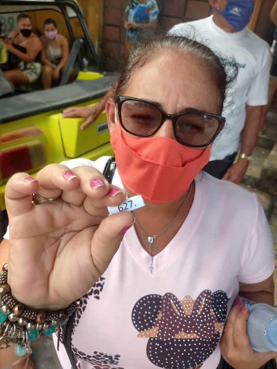 Mulher segura senha para vacinação contra Covid-19 em Cascavel
