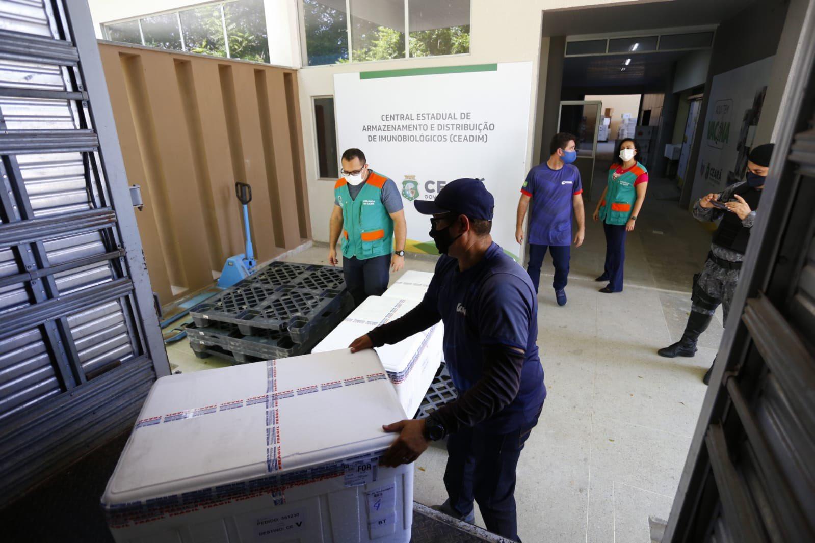 Pessoas distribuindo carga de vacina contra Covid-19
