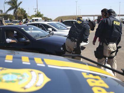 Dois agentes da Polícia Rodoviária Federal abordam veículo