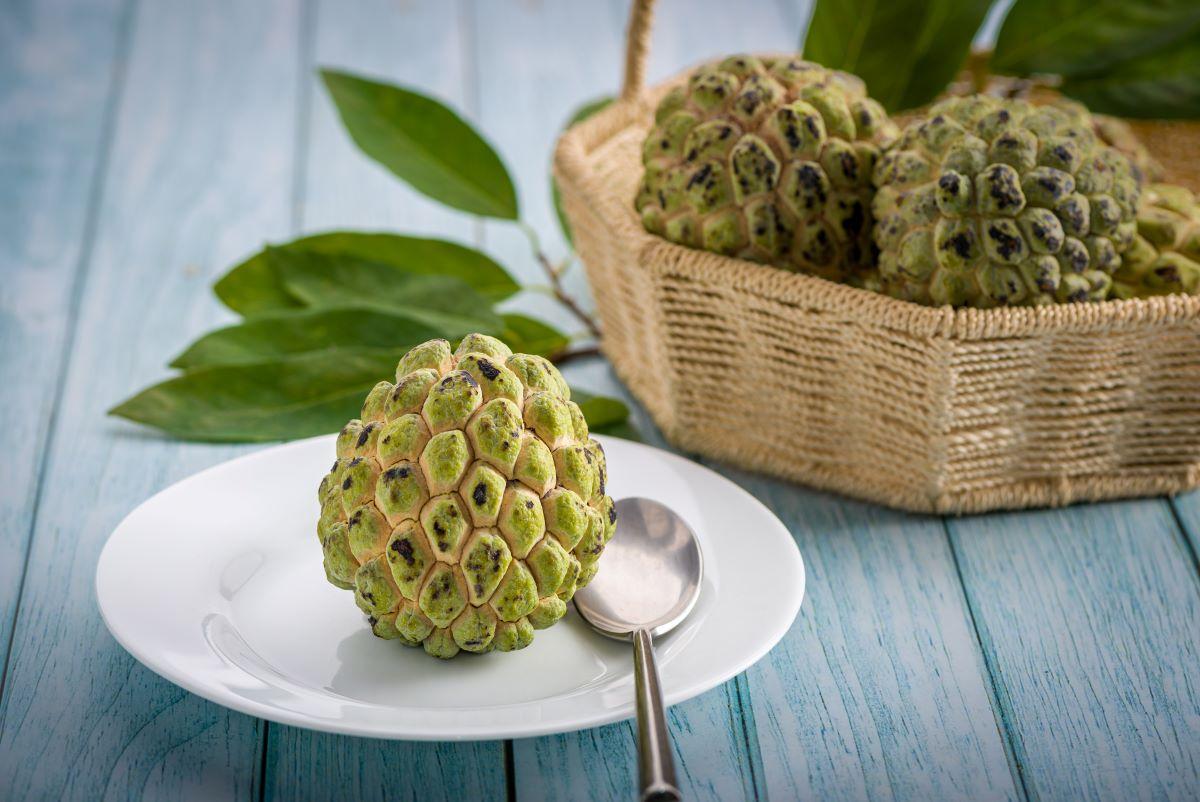 Fruta-do-conde em cima de prato ao lado de colher, com mais frutas ao lado dentro de uma cesta