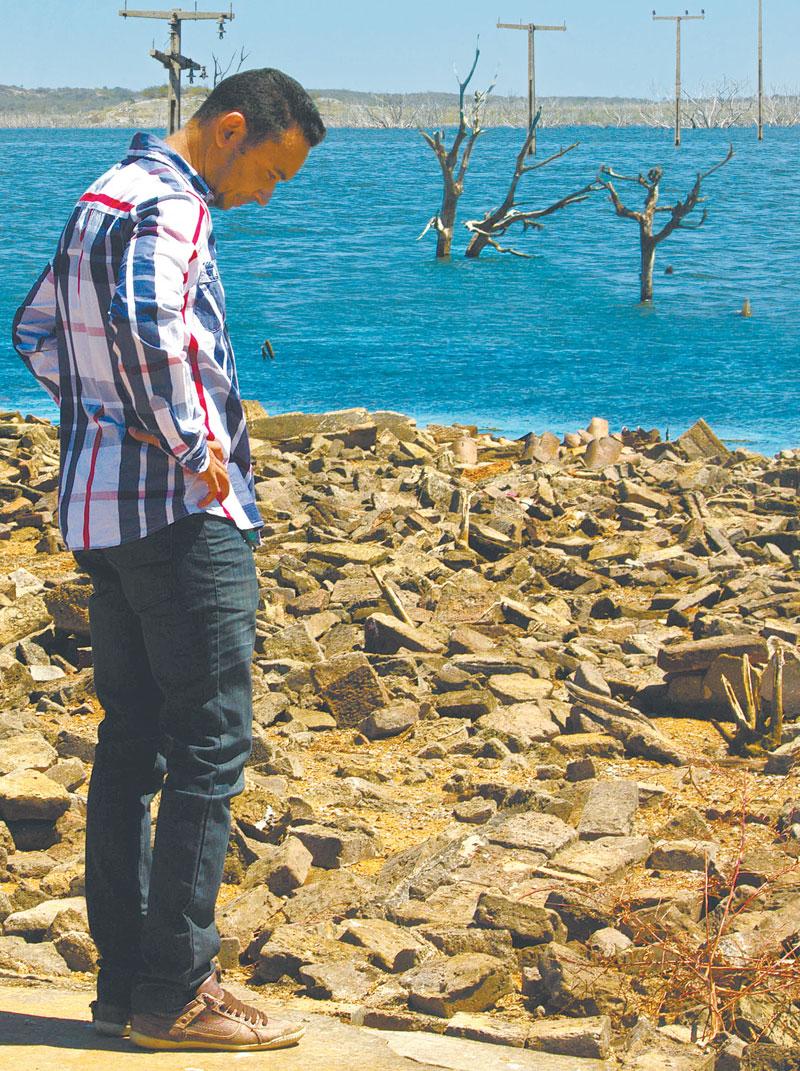 Morador contempla baixo nível hídrico, ressurgindo postes da antiga rede elétrica